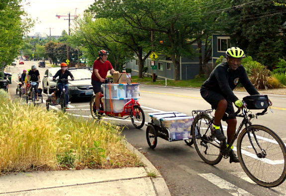 People with bike trailers hauling lots of food up the hill in a bike lane.