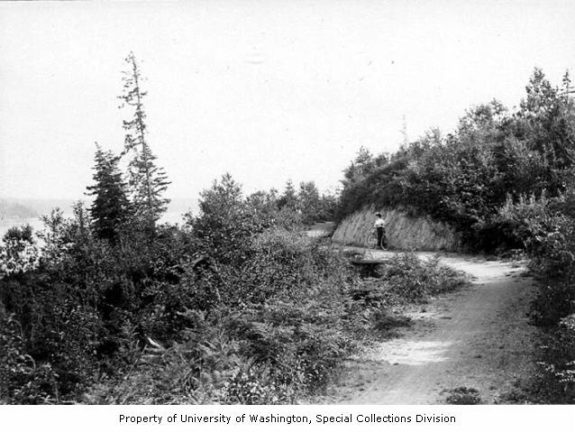 Old photo of a woman with a bike on a winding path.