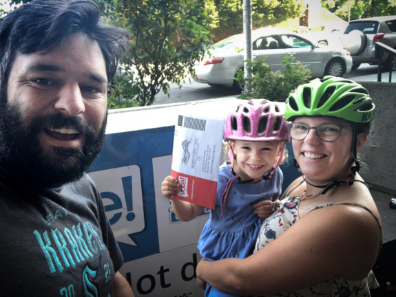 Photo of the author, spouse and 3 year-old in front of a ballot box. The 3 year-old is holding a ballot.