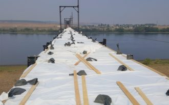 Looking down the under-construction bridge surface. There are no side rails yet.