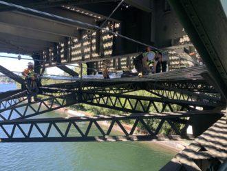 Photot of workers underneath the bridge.
